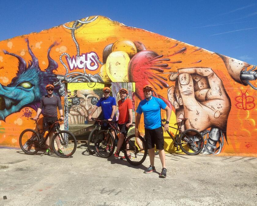 Participants of a bike tour pose in front of a graffiti wall