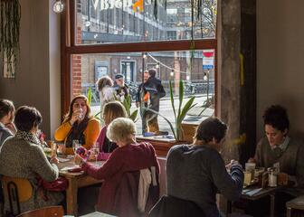 Mensen lunchen aan het zonnige raam